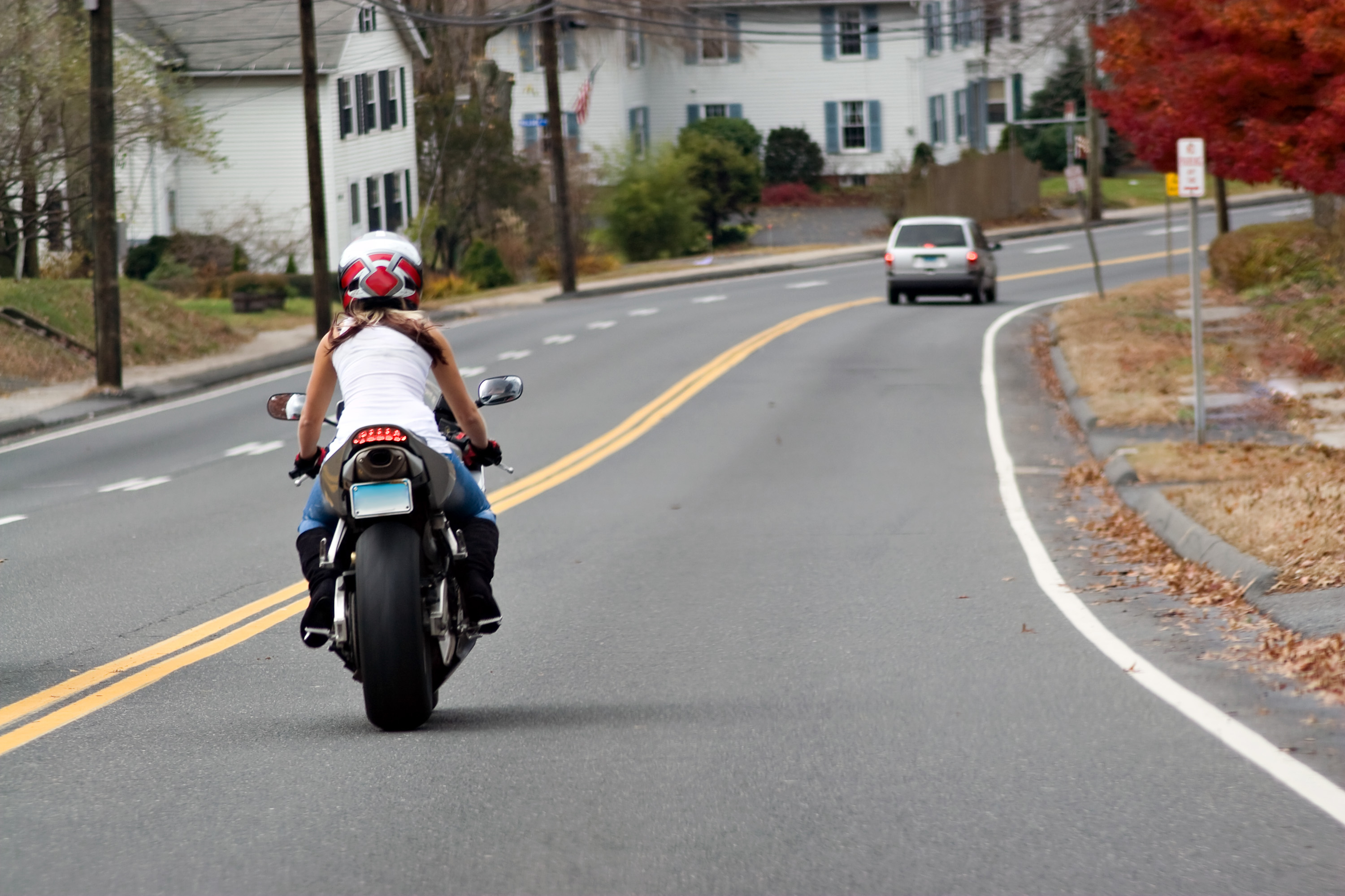 A Young Woman on a Motorcycle Maintains a Safe Following Distance with the Car Ahead